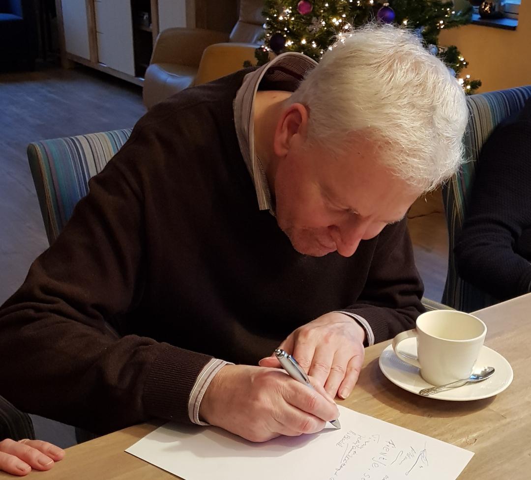 Bewoner van Herbergier Vlijmen zet zijn handtekening